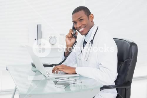 Smiling doctor using phone and laptop at medical office