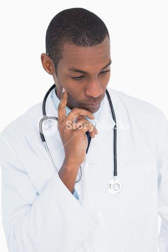 Serious thoughtful male doctor looking down