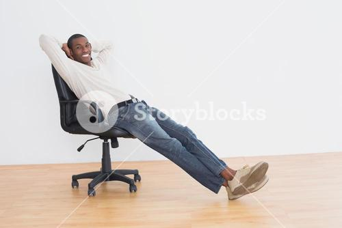 Smiling Afro man sitting on office chair in an empty room