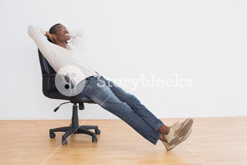 Thoughtful casual Afro man sitting on office chair in empty room