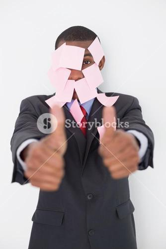 Afro businessman covered in blank notes gesturing thumbs up