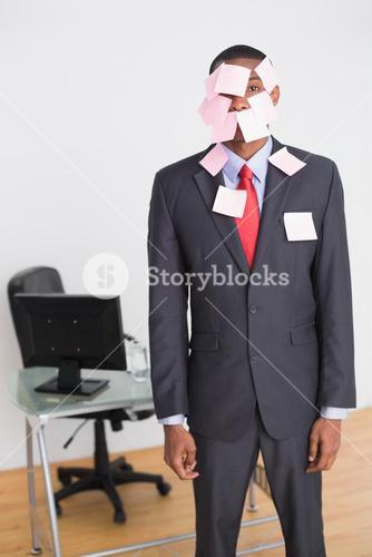 Businessman covered in blank notes at office