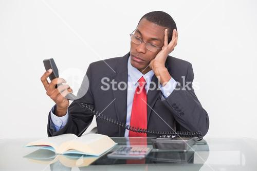 Tensed young Afro businessman looking at telephone receiver