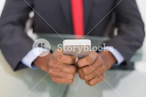 Mid section of well dressed businessman text messaging