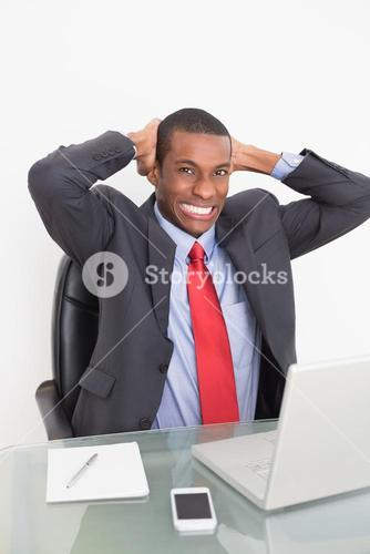 Elegant young Afro businessman with laptop at desk