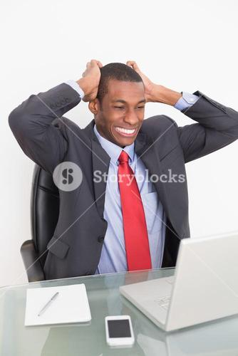 Frustrated Afro businessman looking at laptop at desk