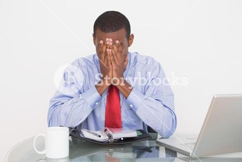 Businessman with hands covering face at desk