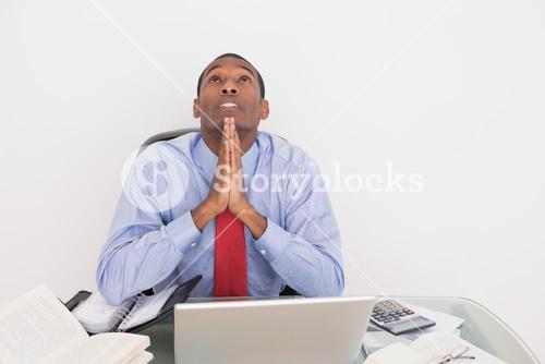 Afro businessman looking up with joined hands at desk