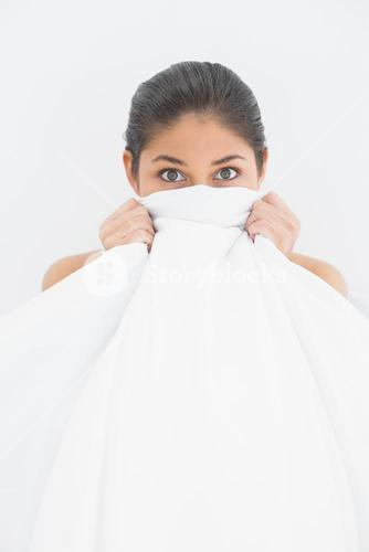 Portrait of a woman covering face with bedsheet in bed