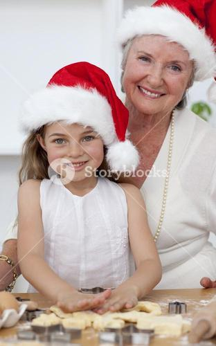 Smiling grandmother and little girl baking Christmas cakes
