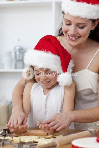Mother and little girl baking Christmas cakes