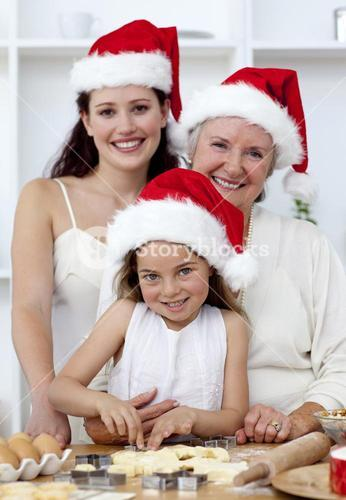 Daughter, mother and grandmother baking Christmas cakes