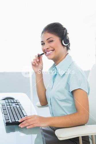 Cheerful businesswoman wearing headset while using computer