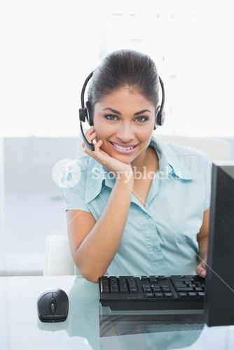 Businesswoman wearing headset while using computer