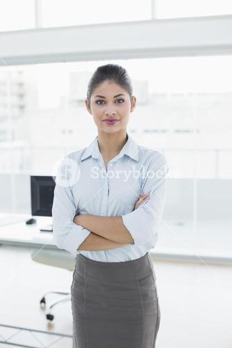 Elegant businesswoman with arms crossed in office