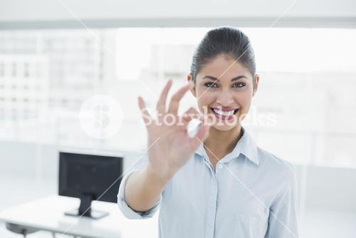 Businesswoman gesturing ok sign in office