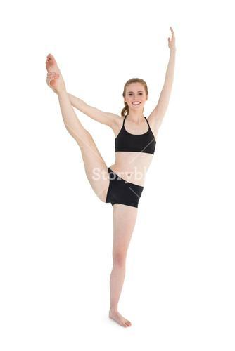 Full length of a sporty young woman stretching leg