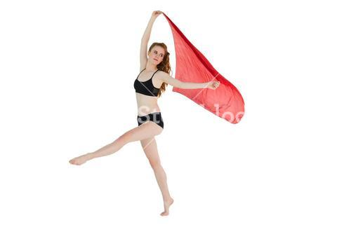 Full length of a sporty woman holding red fabric