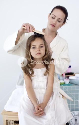 Mother brushing her daughters hair