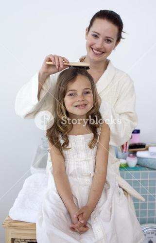 Mother doing her daughters hair