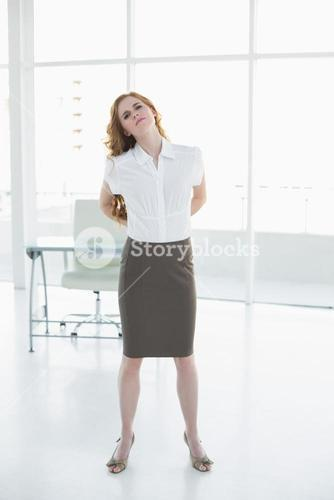 Elegant businesswoman suffering from back ache in office