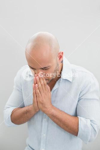 Close up of a sad casual man with hands to his face
