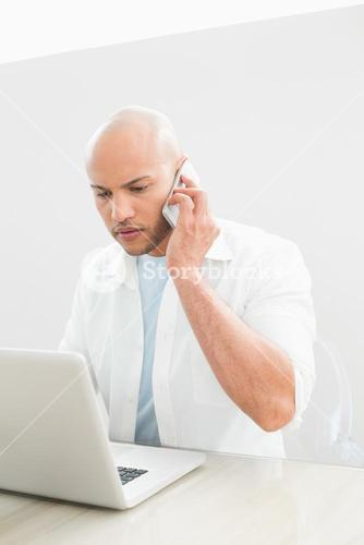 Casual serious man using cellphone and laptop at desk