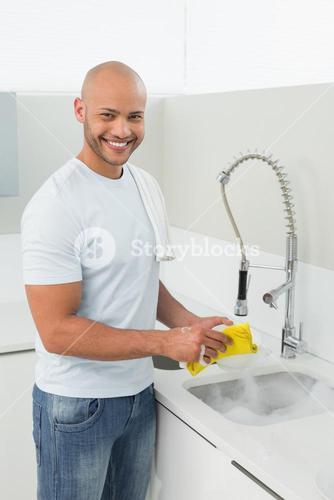 Smiling young man doing the dishes at kitchen sink