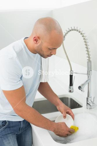 Young man doing the dishes at kitchen sink