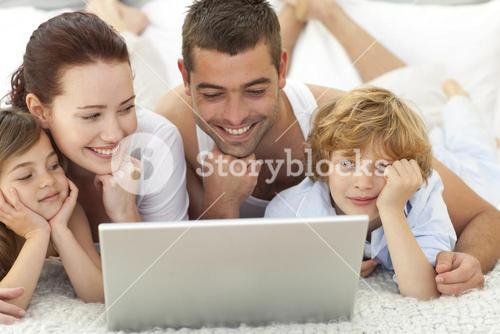 Family in bed playing with a laptop