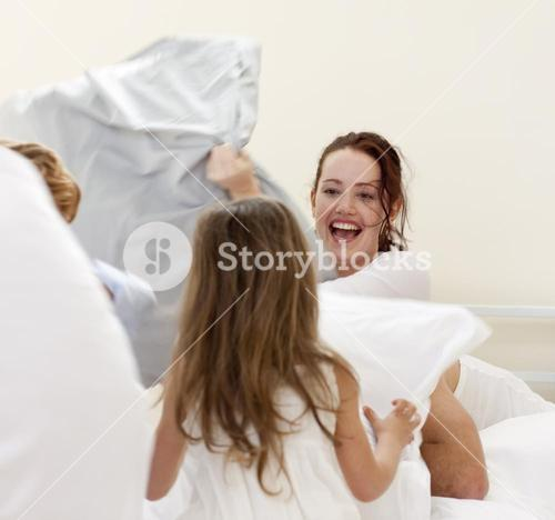 Mother and children having a pillow fight