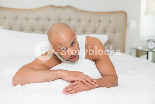 Portrait of a young man resting in bed