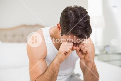 Young man rubbing his eyes in bed