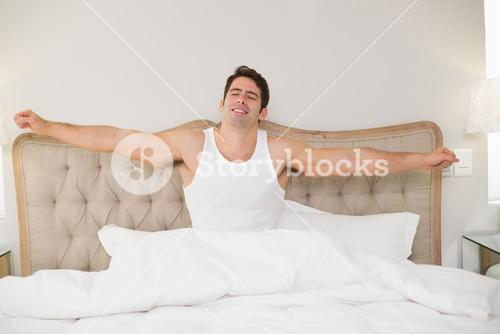 Young smiling man stretching arms in bed