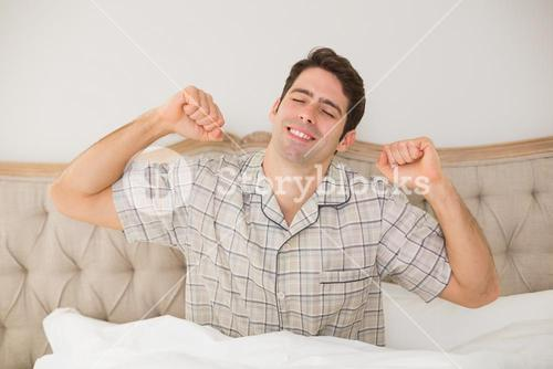 Man waking up in bed and stretching his arms