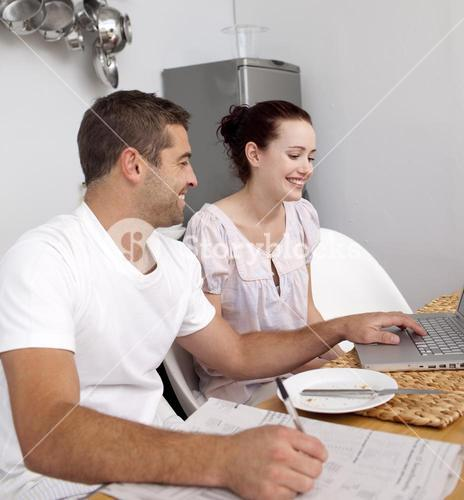 Couple working with a laptop in kitchen
