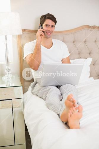 Casual man using cellphone and laptop in bed
