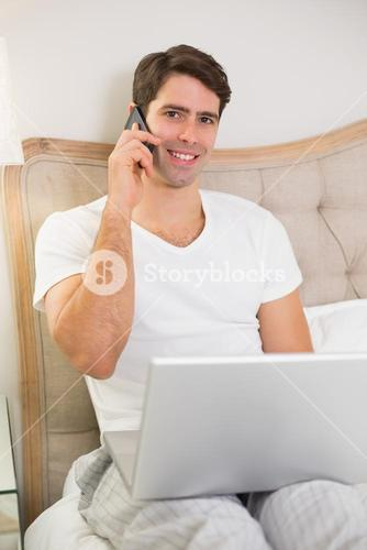 Casual smiling man using cellphone and laptop in bed