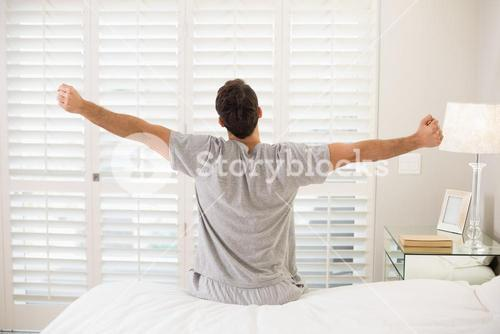 Rear view of a man stretching his arms in bed