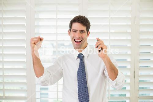 Cheerful businessman with mobile phone clenching fist in office