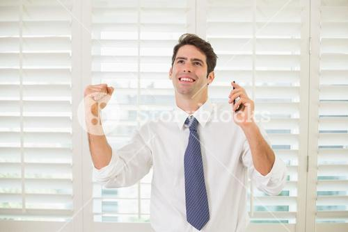 Businessman with mobile phone clenching fist in office