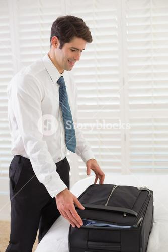 Businessman unpacking luggage at a hotel bedroom