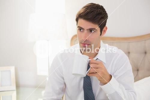 Serious well dressed man drinking coffee in bed