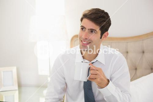 Smiling well dressed man drinking coffee in bed