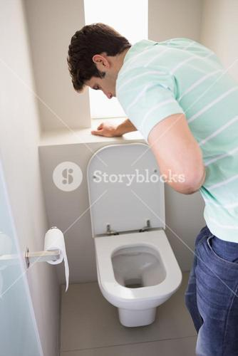 Man with stomach sickness about to vomit into the toilet