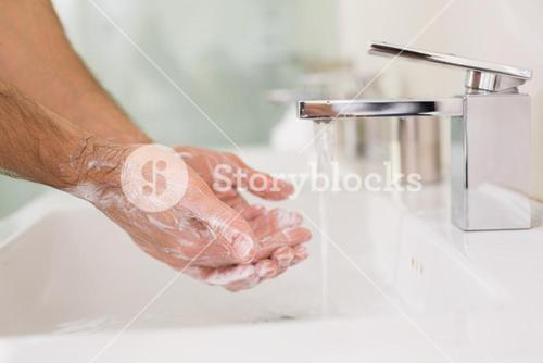 Washing hands with soap under running water at bathroom sink
