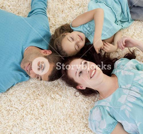 Parents and daughter on floor with heads together