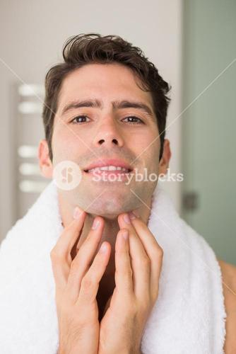 Handsome young man touching his face