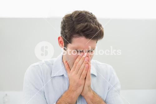 Sad casual young man with hands to his face