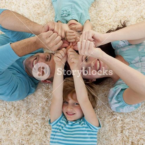 High angle of family on floor with heads and hands together